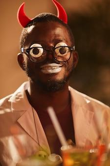 Африканский человек в костюме дьявола на хэллоуин