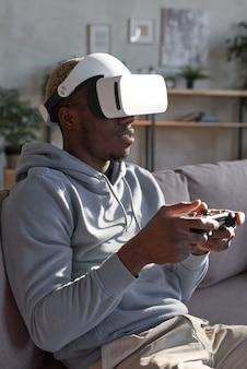 소파에 앉아 조이스틱을 사용하여 집에서 비디오 게임을 하는 안경을 쓴 아프리카 남자
