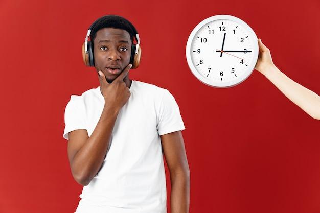 ヘッドフォンでアフリカ人男性は時計の横に彼の顔に手を握ります