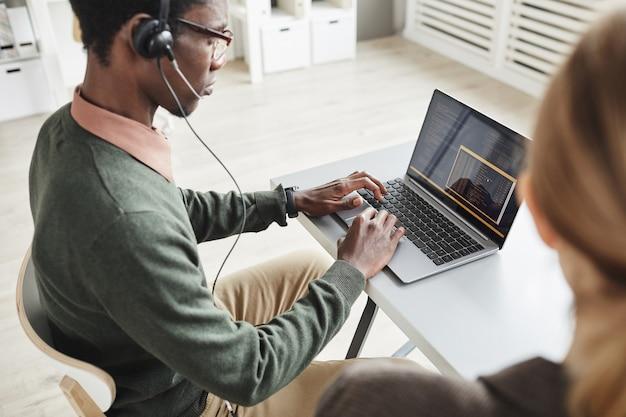 ノートパソコンで入力し、顧客サービスで働いていると話しているヘッドフォンのアフリカ人
