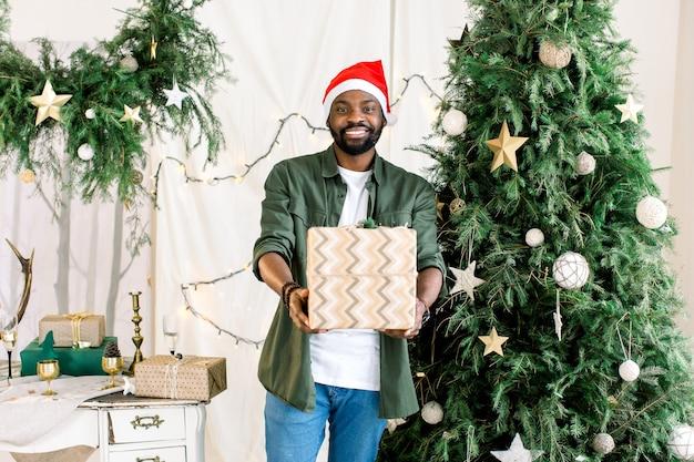 Африканский мужчина в новогодней шапке с подарочной коробкой на фоне елки