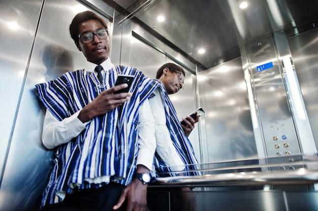 엘라 베이터 또는 현대 리프트에서 휴대 전화와 함께 전통적인 옷과 안경에 아프리카 사람