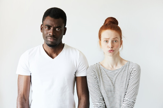 Африканский мужчина в белой футболке и рыжая кавказская женщина в полосатом топе