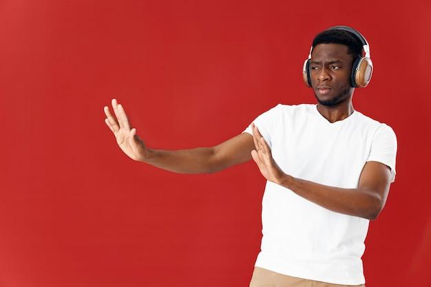 彼の手でヘッドフォンジェスチャーを身に着けている白いtシャツのアフリカ人