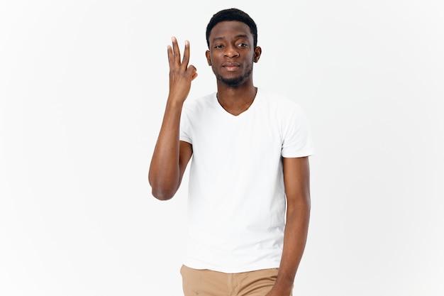 手で身振りで示す白いtシャツのアフリカ人の手でトリミングされたビュー