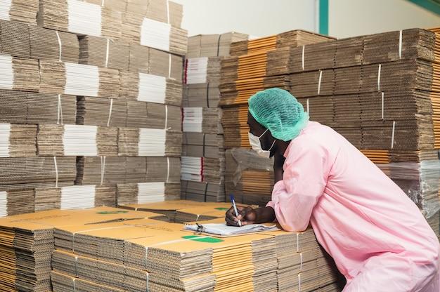 음료 가공 공장의 창고에 쌓여 있는 판지 상자 패키지의 멸균 의류 검사 순서를 확인하는 아프리카 남성 재고 관리 관리자