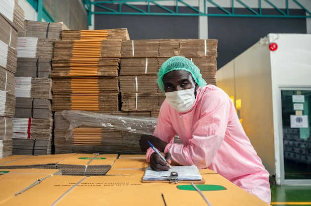 African man inventory control manager in sterile clothing checking order of cardboard box package stacked in warehouse at beverage processing plant