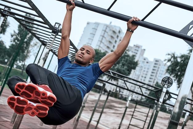 Африканский мужчина делает упражнения на растяжку в тренажерном зале под открытым небом возле парка