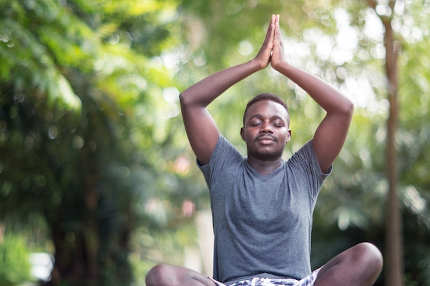 African man is meditating on green grass in the park