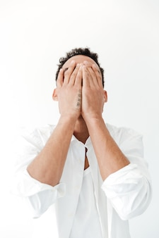African man isolated over white  covering face