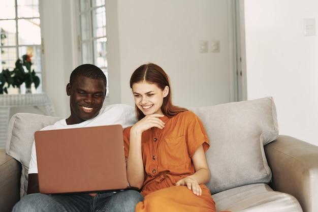 幸せな女の隣に座っているアフリカ人のラップトップ