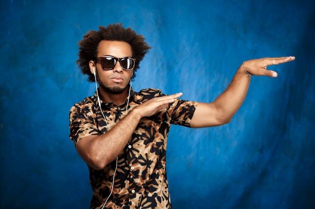 Musica d'ascolto dell'uomo africano in cuffie, ballanti sopra la parete blu.