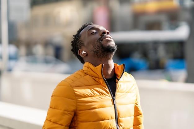 음악을 듣고 야외에서 도시에 서있는 신선한 공기를 호흡하는 아프리카 남자