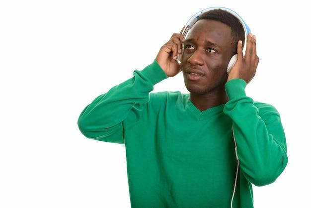 考えながらヘッドフォンで音楽を聴くアフリカ人