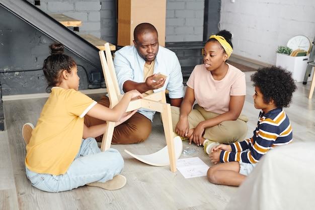 組み立て方について妻、娘、息子と相談しながら、木製の椅子の小さな長方形の部分を見ているアフリカ人男性