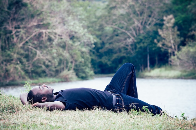 African man lying on the ground in the midst of nature with happy and comfort.
