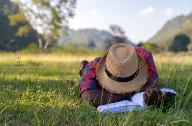 African man lying and sleeping after reading a book on the grass .