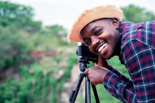 African man photograpy taking the camera and tripod with smiling and happy.
