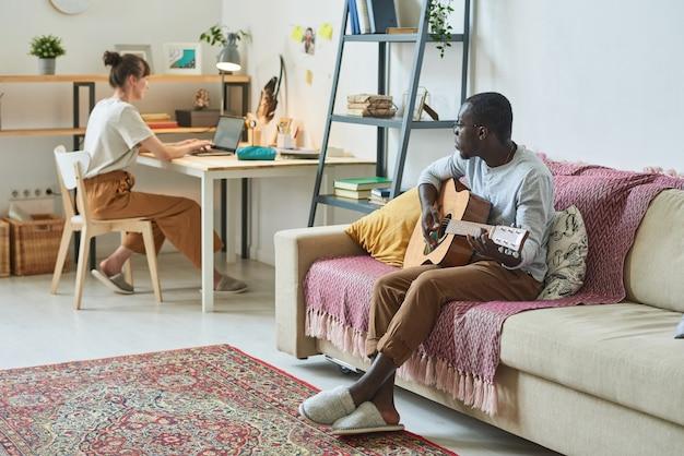 テーブルに座って自宅の部屋でラップトップに取り組んでいる女性とソファでギターを弾くアフリカ人男性