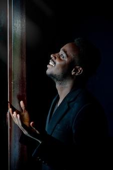 Африканский мужчина молится за бога в темной комнате.