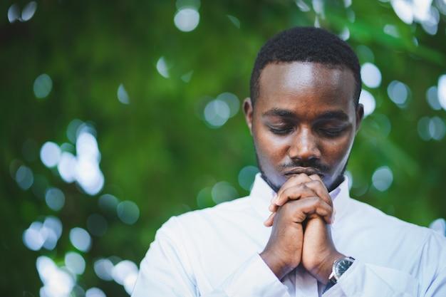 緑の自然の中で神に感謝を祈るアフリカ人