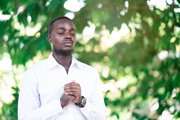 African man praying for thank god in the green nature