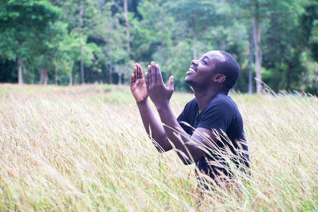 African man praying for thank god with light flare in meadow field.