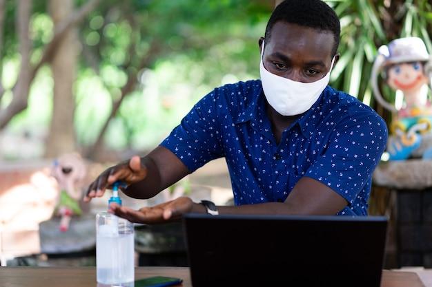 집에서 일하는 동안 코로나 바이러스 질병 (covid-19) 보호를 위해 손을 씻는 아프리카 남자 프레스 살균 젤