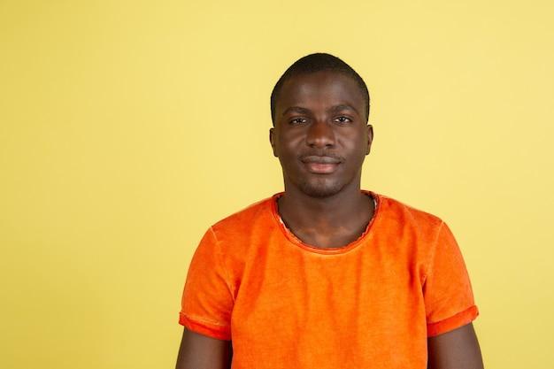 노란색 스튜디오 벽에 고립 된 아프리카 남자의 초상화