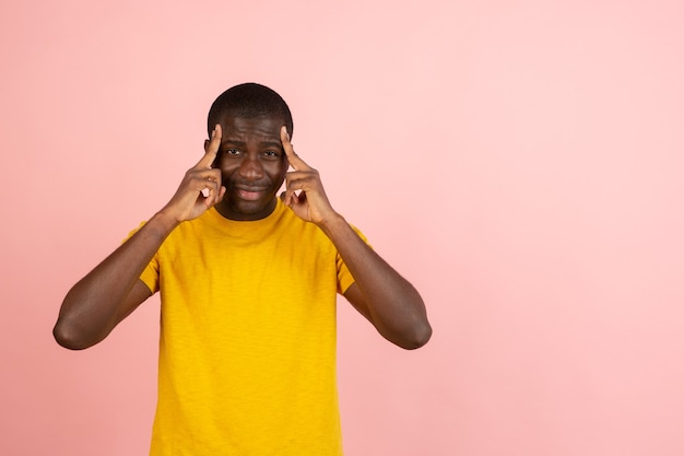 African man's portrait isolated over pink studio wall