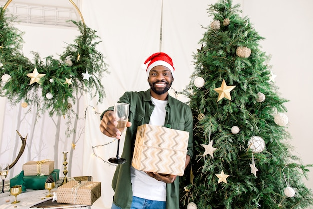 African man in santa hat near christmas tree holding champagne and present gift