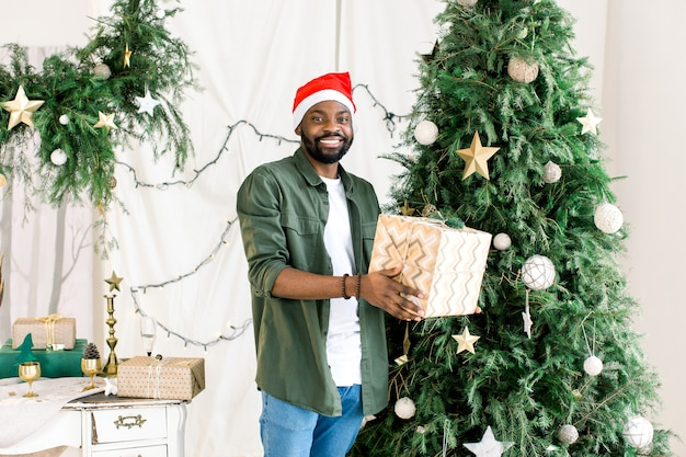 African man in santa hat with gift box on the background of christmas tree