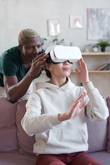 彼女がバーチャルリアリティゲームをプレイしようとしている女性のためのvrメガネにビデオゲームを設定するアフリカの男性