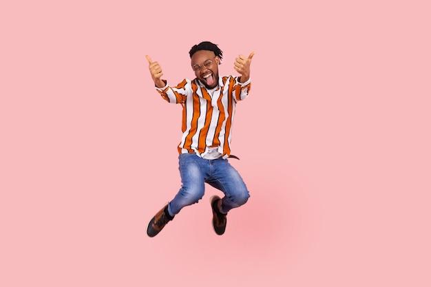 Африканский мужчина показывает палец вверх, высоко прыгает, словно летит