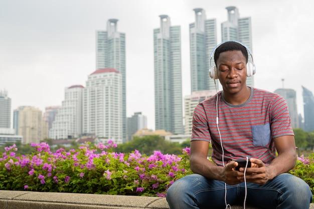 Африканский мужчина сидит в парке, слушая музыку в наушниках и используя мобильный телефон