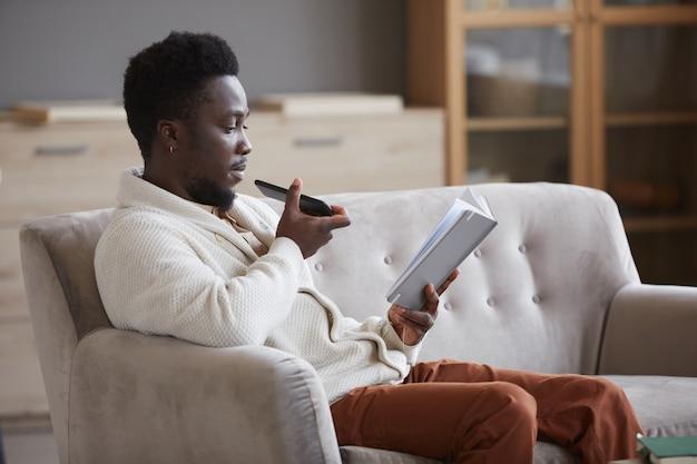 Африканский мужчина сидит на диване, читает книгу и записывает звуковое сообщение на свой мобильный телефон, сидя в комнате