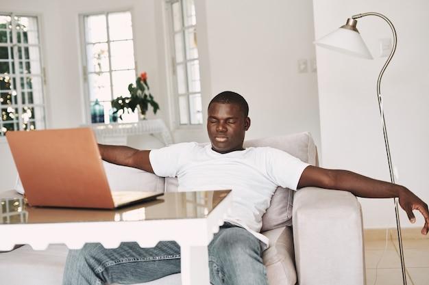 소파에 앉아 테이블에 있는 노트북을 보고 있는 아프리카 남자 프리랜서 모델