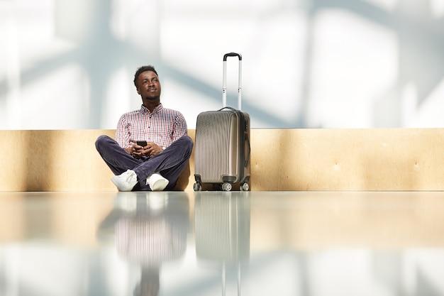 スーツケースを持って床に座って、空港で彼の携帯電話を使用してアフリカ人男性