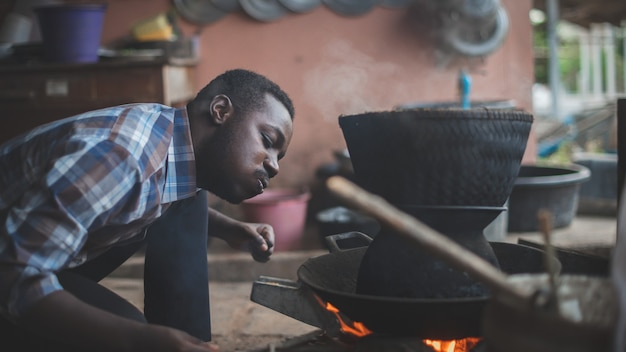 米を調理するために火を吹くために座っているアフリカ人。16:9スタイル