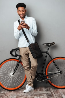 African man standing near bicycle chatting by phone.