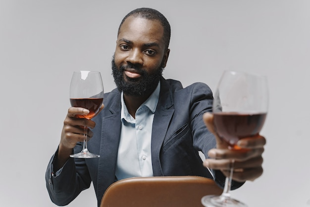 L'uomo africano in uno studio. muro bianco. uomo in giacca e cravatta.