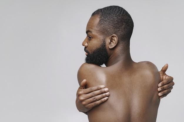 L'uomo africano in uno studio. muro bianco. uomo senza vestiti.