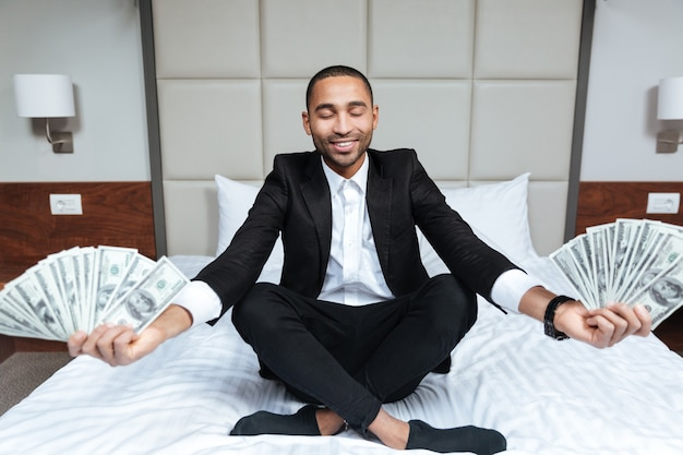 African man in suit meditates with money in hands and closed eyes on bed in hotel room
