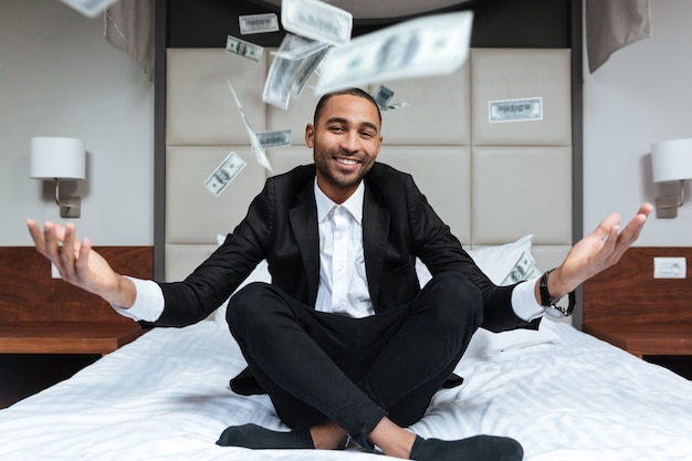 African man in suit throws the money and sitting on bed in hotel room