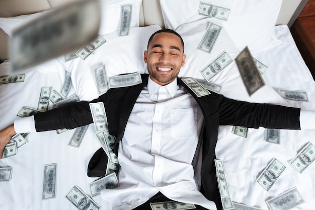 African man in suit with closed eyes lying on bed in hotel room with falling money. top view