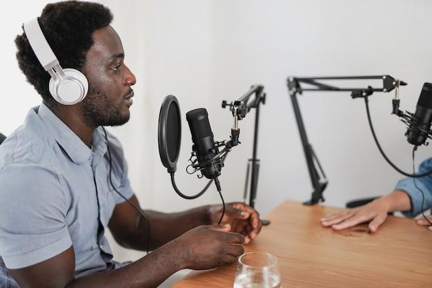 スタジオ内のインタビューポッドキャストで話しているアフリカ人男性