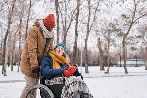 Африканский мужчина разговаривает со своим другом в инвалидной коляске во время прогулки в парке