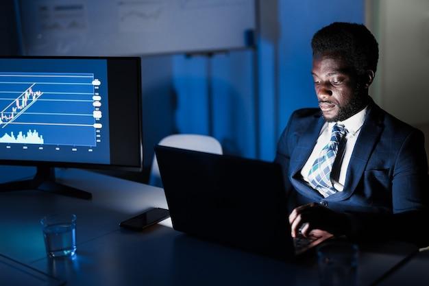 Африканский мужчина-трейдер, работающий в ночное время в офисе хедж-фонда