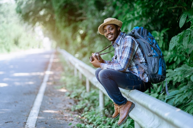 African man traveler carrying backpack and holding camera  side the highway road