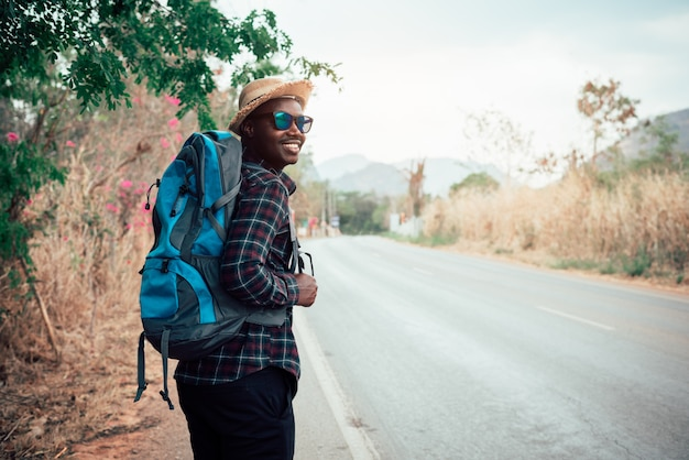 African man traveler carrying backpack walking on the highway road